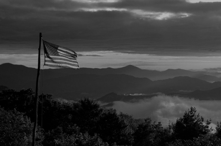 Black and White Image of American Flag flying over Appalachian Mountains